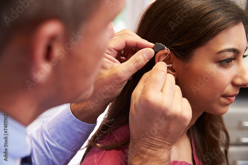 Doctor Fitting Female Patient With Hearing Aid - 74811162