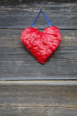 cloth red heart on ancient wooden house wall