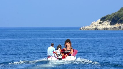 Small boat with people go to rocky island