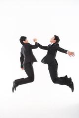 점프하며 하이파이브 하고 있는 두 명의 비즈니스맨