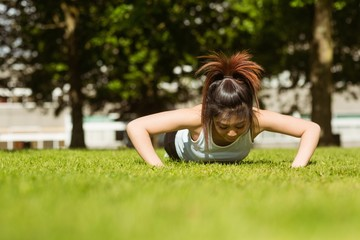 Healthy woman doing push ups in park