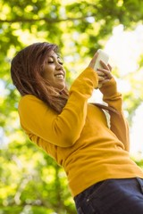 BHeautiful woman text messaging in park