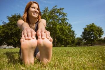 Pretty redhead smiling stretching in park