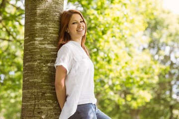 Portrait of a pretty redhead leaning against trunk