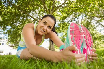 Smiling brunette in sportswear stretching on the grass