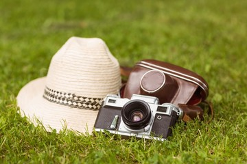 Vintage camera with his cover near a straw hat