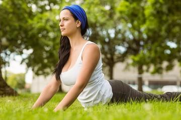 Smiling brunette doing yoga on grass