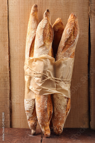 Papiers peints Boulangerie French baguettes in paper on wooden background