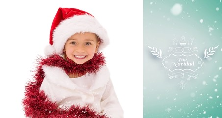 Composite image of cute little girl wearing santa hat and tinsel