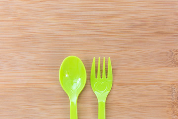 Colorful spoon and fork on wood