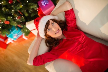 Redhead in santa hat lying on the couch at christmas