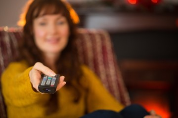 Smiling redhead holding remote control at christmas