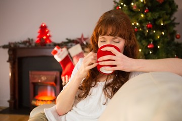 Pretty redhead sitting on couch drinking hot chocolate