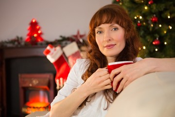 Pretty redhead holding a mug of hot chocolate at christmas