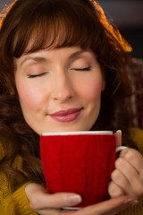 Portrait of redhead enjoying hot drink at christmas