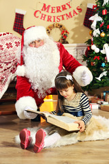 Santa Claus reading book with little cute girl near  fireplace