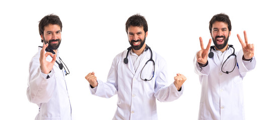 Doctor doing victory gesture over white background