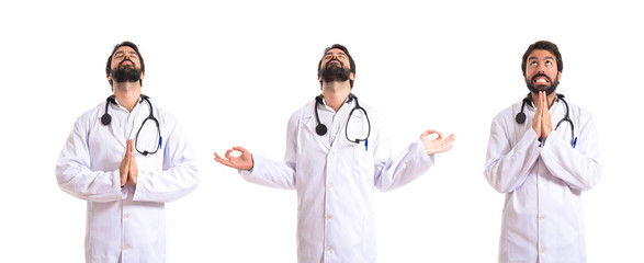 Doctor in zen position over white background