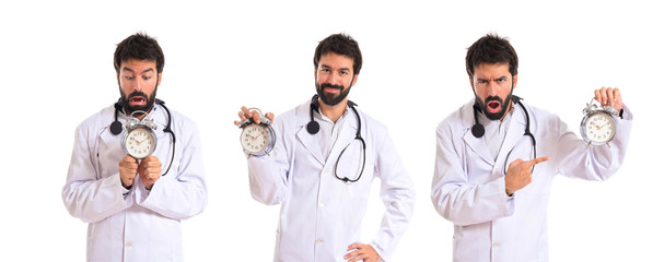 Doctor holding a clock over white background