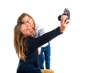 Mother and daughter photographing over white background