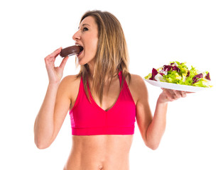 woman undecided between a donut and a salad
