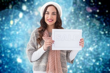 Composite image of brunette in winter clothes holding sale sign