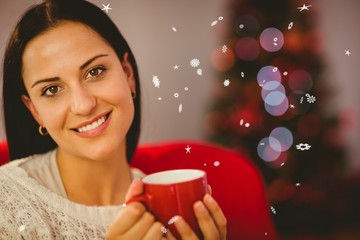 Composite image of pretty brunette relaxing on sofa at christmas