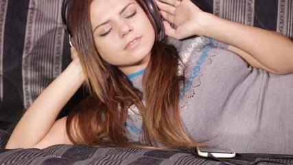 Girl with headphones and smart on sofa