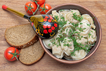 Russian cuisine: dumplings on a plate, cherry tomatoes and bread