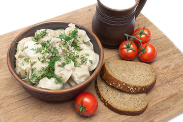 Russian cuisine: dumplings on a plate, tomatoes and bread on the