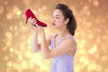 Composite image of elegant brunette kissing a shoe