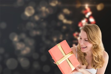 Composite image of cute blonde holding a gift