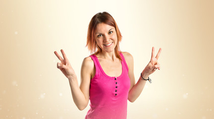 Young woman doing victory gesture over white background