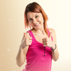 Pretty young girl with thumbs up over white background