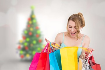 Composite image of excited woman looking at many shopping bags
