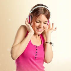 Young girl listening music over white background