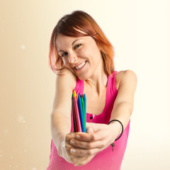 Young redhead girl holding crayons over white background