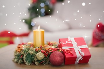 Composite image of candle and wreath on table for christmas