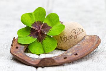 Glücksbringer und Stein auf Holz, Alles Gute