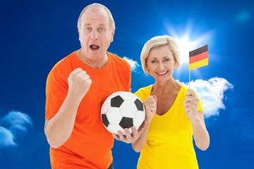 Happy german couple cheering at camera holding