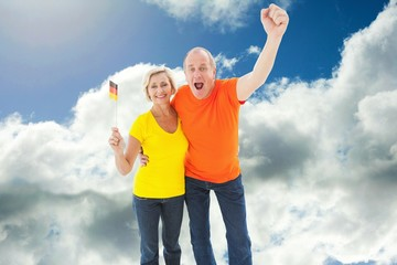 Composite image of happy german couple cheering at camera