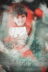 Composite image of festive little boy holding gingerbread house