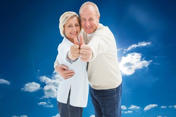Composite image of happy mature couple showing thumbs up
