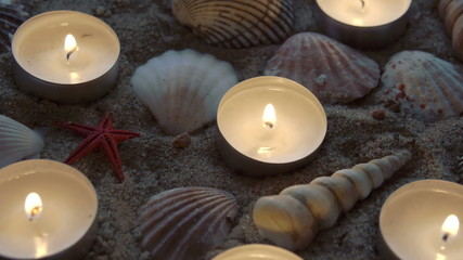 Six candles and some seashells on the sand