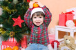 Happy smiling little boy in Santa hat with tangerine