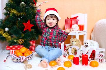 happy 2 years boy in Santa hat sits near Christmas tree