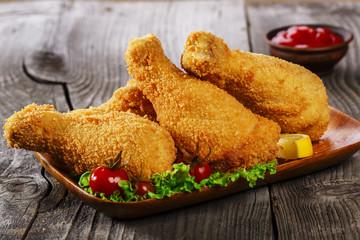 fried chicken leg in breadcrumbs on a wooden surface