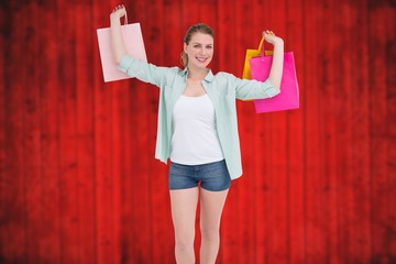 Composite image of smiling young woman holding up shopping bags