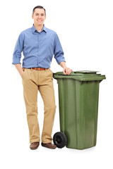 Young man standing by a large green trash can