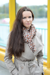 Young beautiful brunette in a gray coat and scarf leopard